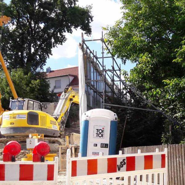 Bild einer Baustelle mit Raupenbagger und Schrankenzaun