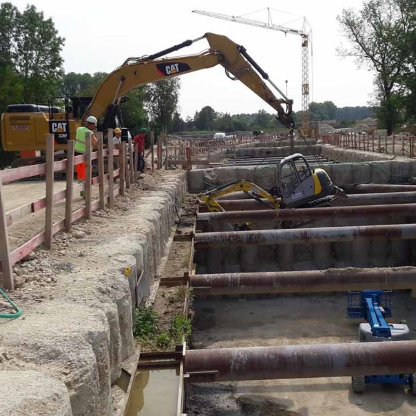 kleiner Mobiler Kettenbagger wird hinabgelassen in Baustellengrube