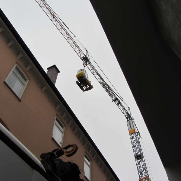 großer Kran transportiert Baumaschine in Freising
