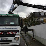 LKW mit Kran hebt Minibagger über Mauer
