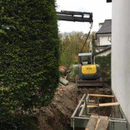 Minibagger wird zur Baustelle im Garten gehoben